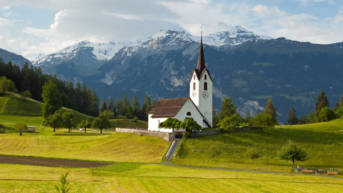 Switzerland-Alps-mountains-grass-trees-church-sky-clouds_1920x1080